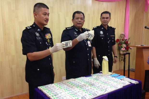 ACP Zainol Samah shows the media the fake money