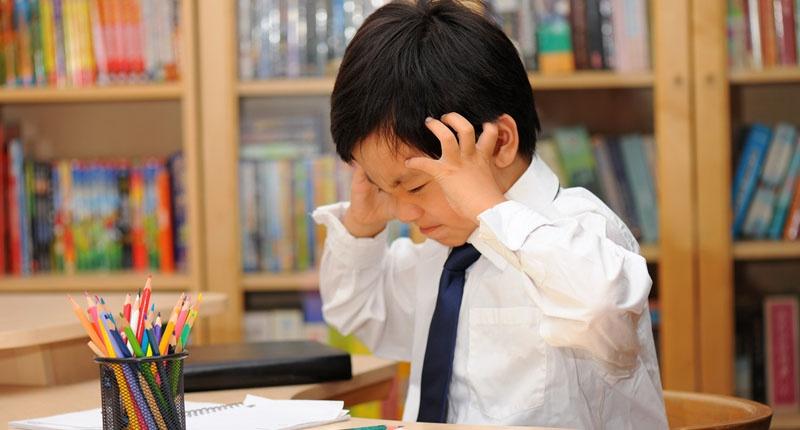 Frustrated-Asian-schoolboy-in-school-uniform-doing-homework-Shutterstock-800x430