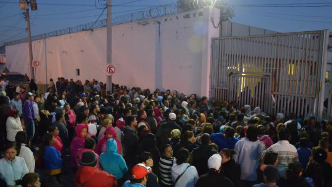 In this Thursday, Feb. 11, 2016 photo, relatives of inmates stand outside the Topo Chico prison, where a riot broke out overnight in Monterrey, Mexico. Dozens of inmates were killed and several injured in a brutal fight between two rival factions at the prison in northern Mexico, according to the state governor. (AP Photo/Emilio Vazquez)