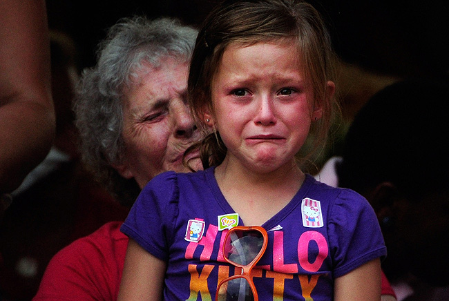 AURORA, CO - JULY 22: Family members react as the names of the 12 victims of the mass shooting at Century 16 movie theater are read aloud during a prayer vigil at the Aurora Municipal Center July 22, 2012 in Aurora, Colorado. Suspect James Holmes, allegedly went on a shooting spree and killed 12 people and injured 59 during an early morning screening of 'The Dark Knight Rises.' (Photo by Aaron Ontiveroz-Pool/Denver Post via Getty Images)