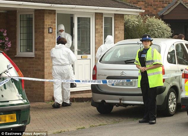 Scene: Police officers outside the house where Mrs Kalejaiye was killed in September 2013