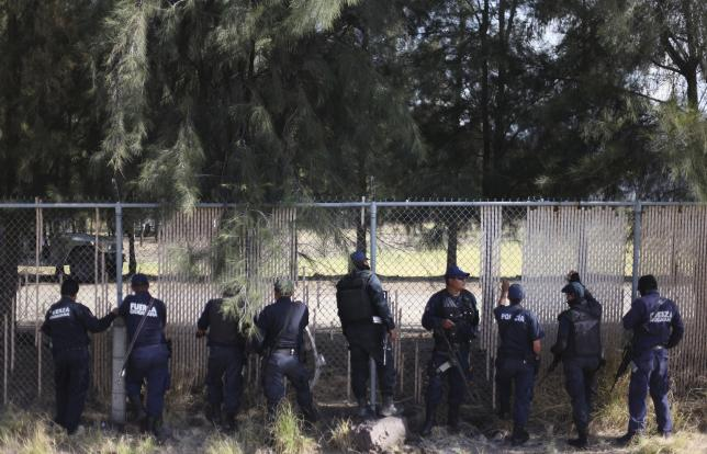 Federal policemen guard a ranch where a gunfight between hitmen and federal forces left several casualties in Tanhuato
